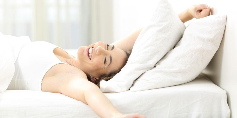 Fröhliche Frau streckt sich genüsslich in Ihrem Bett