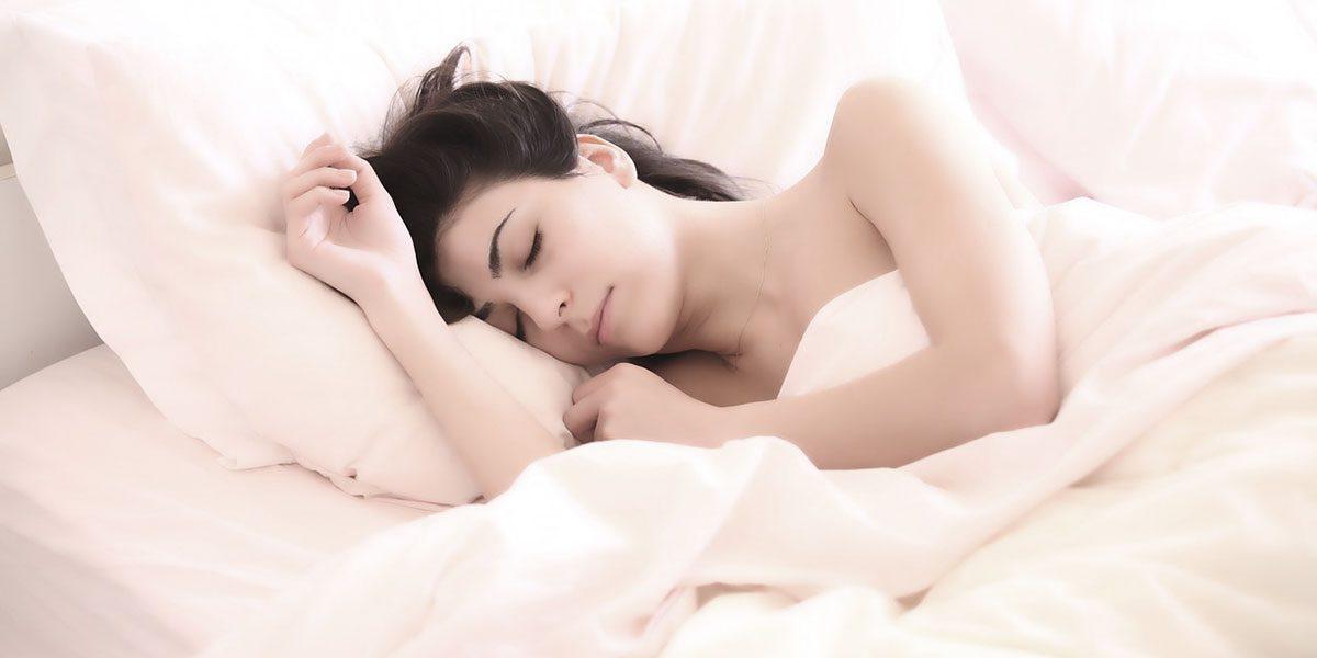Frau schläft im Bett bei sommerlichen Temperaturen
